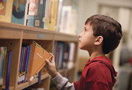 Boy taking book shelf